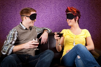 Man and woman in blindfolds having a blind date