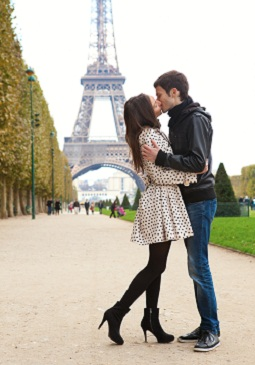 Tall guy kissing shorter girl near Eiffel tower