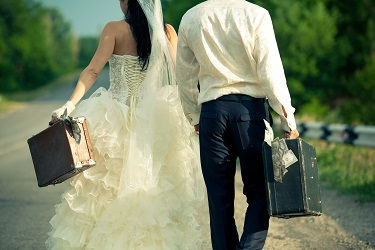 Man and woman in wedding attire holding suitcases of money