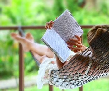 Woman reading a book in hammock